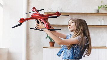 Girl holding red toy drone