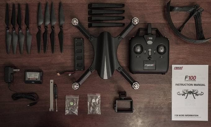 F100 Brushless Drone unboxing on wooden floor