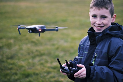A young boy flying a drone and smiling